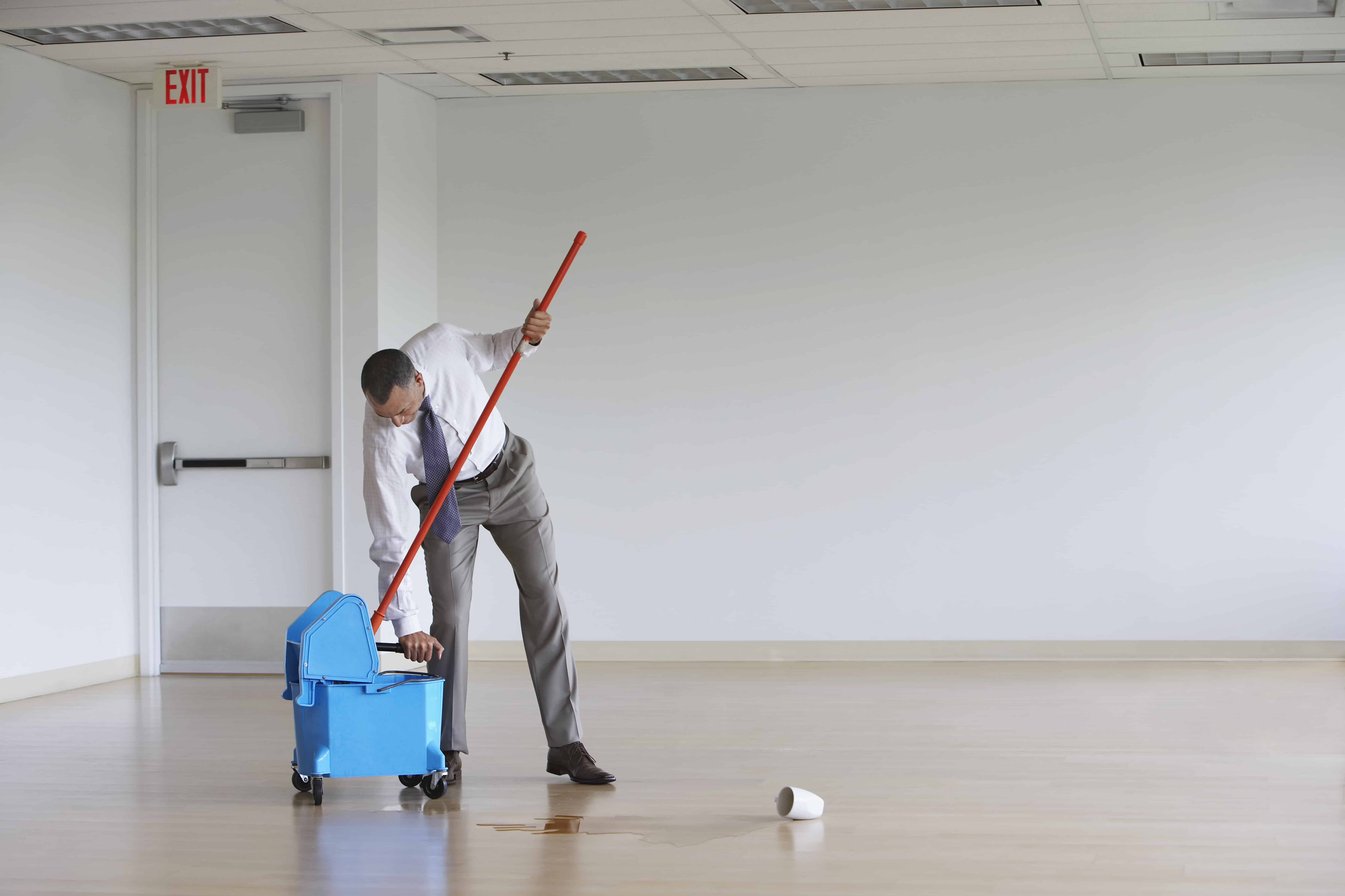 Business man mopping in empty room